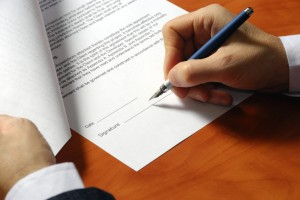 contract signing close up of hand and pen